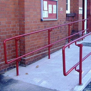 A red DDA handrail system installed on an access ramp